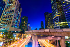 Photo of commercial office buildings exterior. Night view at bot. Tom skyscrapers with light of traffic rush, long exposur in Bangkok Stock Image