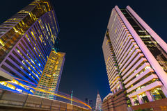 Photo of commercial office buildings exterior. Night view at bot. Tom skyscrapers with light of traffic rush, long exposur in Bangkok Stock Photo
