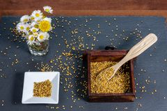Photo composed of a square bowl of white ceramic, a wooden box full of pollen grains of bees and a bunch of daisies, on a slate. Board, top view stock photos