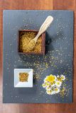 Photo composed of a square bowl of white ceramic, a wooden box full of pollen grains of bees and a bunch of daisies, on a slate. Board, top view stock photo