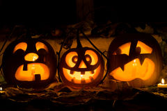 Photo composition from three pumpkins on Halloween. Crying, mad and afraid of some pumpkin against an old window, leaves and candles Stock Image