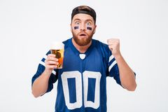 Concentrated man fan in blue t-shirt drinking beer. Photo of concentrated man fan in blue t-shirt standing isolated over white background. Looking camera Royalty Free Stock Photography
