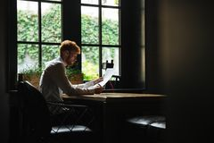 Photo of concentrated readhead bearded businessman reading contr Royalty Free Stock Image