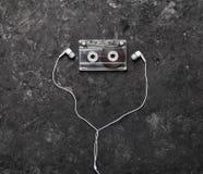 Photo conceptuelle illustrant l'amour de la musique Cassette sonore et écouteurs sur un fond concret noir Vue supérieure Image libre de droits