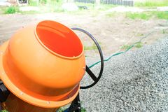 Photo concrete mixer installed on the construction site next to a pile of sand and gravel.  royalty free stock image