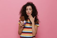 Photo of confused woman 20s with curly hair holding chocolate ba. R isolated over pink background stock images