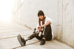 Photo of content handicapped woman having bionic leg in streetwear, sitting on concrete floor outdoor and looking at wristwatch w. Photo of content handicapped royalty free stock photography