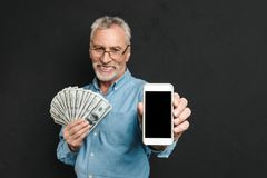 Photo of content retired man 60s with gray hair holding fan of m. Oney dollar cash and demonstrating cell phone on camera isolated over black background Stock Photography