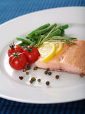 Cooked salmon dinner. Photo of a cooked salmon steak with rosemary, lemon slices, cherry tomatoes, green beans, and peppercorns on a white plate Stock Photos