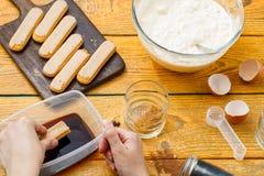 Photo of cooking tiramisu, human hands with savoyardi cookies. Coffee, cups, cheese on wooden table stock photo