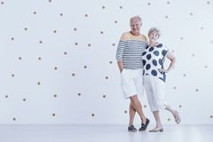 Photo with copy space. Of couple of elders smiling and standing in an empty room with dotted wall royalty free stock image