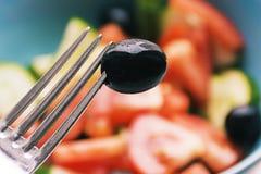 Photo couleur des légumes de salade sur la fourchette de plat avec l'olive photographie stock