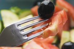 Photo couleur des légumes de salade sur la fourchette de plat avec l'olive image stock