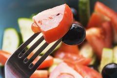 Photo couleur des légumes de salade sur la fourchette de plat avec l'olive et la tomate photos stock