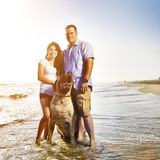 Photo of a couple walking pet dog by the ocean. Stock Photo
