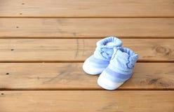 Photo courante : Chaussettes de bébé bleu sur une table en bois Photos stock