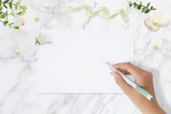 Photo courante dénommée Maquette féminine de bureau de mariage Carte de voeux Fleurs, papier, stylo, bande sur le marbre sensible photographie stock