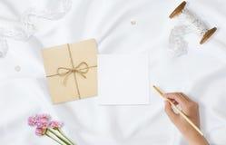 Photo courante dénommée Maquette féminine de bureau de mariage Carte de voeux Fleurs, papier, stylo, bande sur le satin sensible image stock