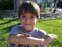 Photo courante de garçon jouant avec la sauterelle Photographie stock libre de droits