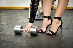 Photo courante de la femme dans des chaussures de talons hauts par l'haltère à Photographie stock