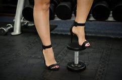 Photo courante de la femme dans des chaussures de talons hauts par les haltères à Image libre de droits