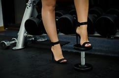Photo courante de la femme dans des chaussures de talons hauts par les haltères à Photos libres de droits
