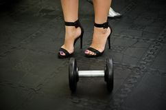 Photo courante de la femme dans des chaussures de talons hauts par les haltères à Images libres de droits
