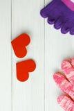 Photo courante : Deux coeurs en bois avec les chaussettes, gants sur un Ba en bois Photographie stock libre de droits