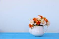 Photo courante : fleurs et vase en plastique sur le plancher en bois Photographie stock