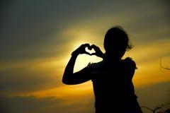 Photo courante - la silhouette de femmes fait le coucher du soleil de forme de coeur Images libres de droits