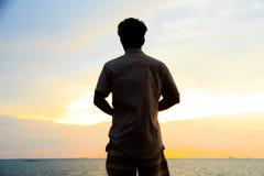 Photo courante - silhouette d'action simple d'homme au coucher du soleil Images stock