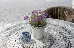 Photo of cozy cafe table on paving stone street in the sunny summer morning with beautiful flowers on lace tablecloth stock image