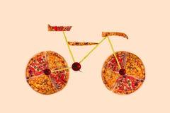 Photo créative de bicyclette de route faite de pizza et légumes internationaux sur le fond blanc delivery photos libres de droits