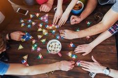 Photo créative de vue supérieure des amis s'asseyant à la table en bois avoir l'amusement tout en jouant le jeu de société Photographie stock libre de droits