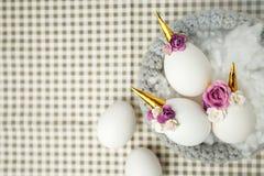 Photo créative mignonne avec les oeufs de pâques dans le nid, licorne avec le décor de fleur - idée créative pour la partie d'est image stock
