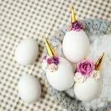 Photo créative mignonne avec les oeufs de pâques dans le nid, licorne avec le décor de fleur - idée créative pour la partie d'est photos libres de droits
