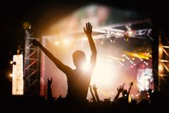 Photo of a crowd, people enjoying rock concert, raised up hands and clapping of pleasure, active night life concept stock images