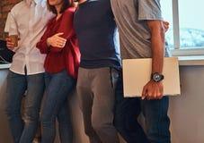 Photo cultivée d'un groupe d'étudiants interraciaux avec l'ordinateur portable dans un dortoir d'étudiant image stock