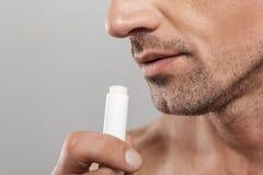 Photo cultivée de l'homme mûr bel tenant le baume à lèvres photographie stock