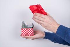 Photo cultivée de profil de côté de l'apparence des mains de l'étudiant tenant le petit petit paquet rouge non emballé complèteme photo stock