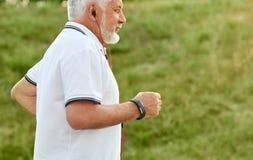 Photo cultivée de vieil homme écoutant la musique tout en courant photos stock