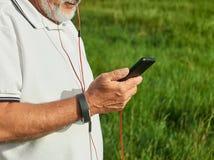 Photo cultivée de vieil homme vérifiant le temps tout en courant dehors image stock