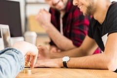 Photo cultivée des amis s'asseyant à une table et jouant avec le gol Photographie stock