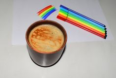 Photo of a cup of coffee on a background of a magnetic board and felt-tip pens. A saturated coffee color with an airy foam and a b stock image