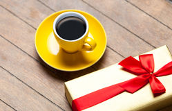 Photo of cup of coffee and cute wrapped gift on the wonderful br Royalty Free Stock Image
