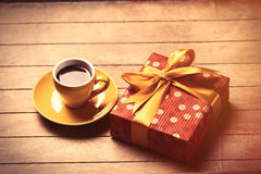 Photo of cup of coffee and cute wrapped gift on the wonderful br Royalty Free Stock Photo