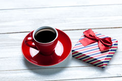 Photo of cup of coffee and cute wrapped gift on the wonderful wh Royalty Free Stock Image