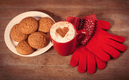 Photo of cup of coffee, plate full of cookies and warm gloves  Stock Images