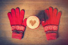 Photo of cup of coffee and warm gloves on the wonderful brown  Stock Images