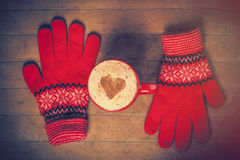 Photo of cup of coffee and warm gloves on the wonderful brown  Royalty Free Stock Photo